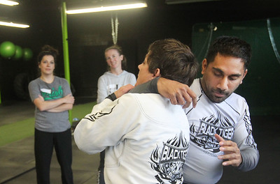 Candace H. Johnson-For Shaw Media Instructor Julie Bond, of Third Lake (center) works with her assistant, Imran Faizi, of Lake Villa on showing her class self-defense techniques during the Women's Self-Defense Seminar presented by Black Tiger Martial Arts at Prime Athletics in Grayslake. The next seminar is on December 7th from 12-1:30 pm. at Prime Athletics.  (11/2/19)