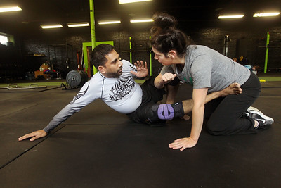 Candace H. Johnson-For Shaw Media Imran Faizi, of Lake Villa, assistant coach, works with Denise Niehus, of Antioch on self-defense techniques during the Women's Self-Defense Seminar presented by Black Tiger Martial Arts at Prime Athletics in Grayslake.  (11/2/19)