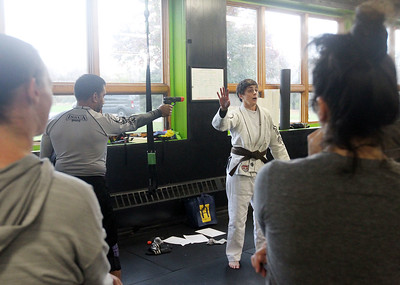 Candace H. Johnson-For Shaw Media Instructor Julie Bond, of Third Lake (center) works with her assistant, Imran Faizi, of Lake Villa on showing her class how to defend yourself if someone has a gun during the Women's Self-Defense Seminar presented by Black Tiger Martial Arts at Prime Athletics in Grayslake.  The next seminar is on December 7th from 12-1:30 pm. at Prime Athletics. (11/2/19)