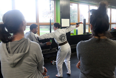Candace H. Johnson-For Shaw Media Instructor Julie Bond, of Third Lake (center) works with her assistant, Imran Faizi, of Lake Villa on showing her class how to defend yourself if someone has a gun during the Women's Self-Defense Seminar presented by Black Tiger Martial Arts at Prime Athletics in Grayslake.  (11/2/19)