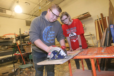 Candace H. Johnson-For Shaw Media Carter Kraus, of Round Lake Beach stands next to Carly Zukowsky, of Fox Lake, both, 17, and set designers, as he uses a circular saw to make steps for the platform on stage in the Scene Shop during technical preparation for Midsummer Night's Dream by William Shakespeare at Grant Community High School in Fox Lake. The play runs on Friday, November 22nd at 7:00 pm, Saturday, November 23rd at 7:00 pm and Sunday, November 24th at 2:00 pm. (11/19/19)