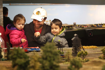 Candace H. Johnson-For Shaw Media Phil Krawchuk, of Barrington holds his children Gwendolyn, 2, and George, 4, as they watch a Metra model train go by during the Lake County Model Railroad Club's Fall Open House in Wauconda. (11/16/19)