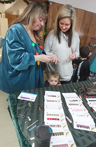 Candace H. Johnson-For Shaw Media Annie Baker-Berglund, of Spring Grove puts a sample of a Color Street nail polish strip on Tina Sullivan, of Lake Villa as she stands next next to her sons, Colson, 1, and Reese, 6, during the Venetian Village Craft Show in Lake Villa. (11/16/19)