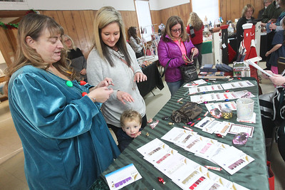 Candace H. Johnson-For Shaw Media Annie Baker-Berglund, of Spring Grove puts a sample of a Color Street nail polish strip on Tina Sullivan as she stands next to her son, Colson, 1, and her mother, Tammie Washburn, all of Lake Villa during the Venetian Village Craft Show in Lake Villa. (11/16/19)