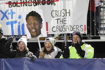 Candace H. Johnson-For Shaw Media Heidi and Dennis Dahlke stand next to Julie Vrabel, (center) all of Gurnee, while she holds a sign with a picture of Malachi McNeal (#9) as they cheer on the Warren varsity football team as they play Brother Rice during the Class 8A state semifinals at Warren Township High School in Gurnee. Warren won 28-0. (11/23/19)