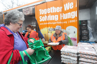 Candace H. Johnson-For Shaw Media Debra Villarreal gets some eggs from Gabriella Galvez, both of Round Lake Beach, a volunteer, at the Rx Mobile Pantry at the Round Lake Library. The next pantry will arrive at the library on December 3rd from 12-2:00 pm. (11/19/19)