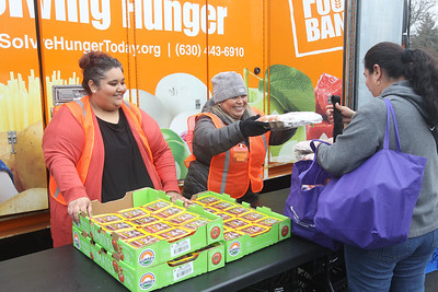 Candace H. Johnson-For Shaw Media Martha Delgado, of Round Lake, receptionist with Avon Township and Gabriella Galvez, of Round Lake Beach, a volunteer, hand out tomatoes and eggs to clients at the Rx Mobile Pantry at the Round Lake Library. The next pantry will arrive at the library on December 3rd from 12-2:00 pm. (11/19/19)