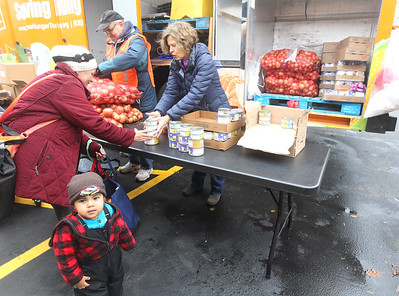 Candace H. Johnson-For Shaw Media Volunteers Wayne Vivirito and Jill Hevrdejs, both of Lake Villa help Julia Chavez, of Waukegan and her son, Isaac, 1, get food including cans of tuna at the Rx Mobile Pantry at the Round Lake Library. The next pantry will arrive at the library on December 3rd from 12-2:00 pm. (11/19/19)