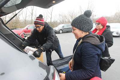 Candace H. Johnson-For Shaw Media Isaac Martinez, of McHenry, operations assistant manager with Avon Township, helps Maria Aguilar and Consuelo Perales, both of North Chicago load food into their car from the Rx Mobile Pantry in the parking lot of the Round Lake Library. The next pantry will arrive at the library on December 3rd from 12-2:00 pm. (11/19/19)