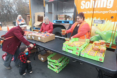 Candace H. Johnson-For Shaw Media Julia Chavez, of Waukegan and her son, Isaac, 1, get tomatoes from Martha Delgado, of Round Lake, receptionist with Avon Township, at the Rx Mobile Pantry at the Round Lake Library. The next pantry will arrive at the library on December 3rd from 12-2:00 pm. (11/19/19)