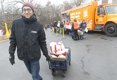Candace H. Johnson-For Shaw Media Isaac Martinez, of McHenry, operations assistant manager with Avon Township, helps a client load food from the Rx Mobile Pantry into their car in the parking lot of the Round Lake Library. The next pantry will arrive at the library on December 3rd from 12-2:00 pm. (11/19/19)