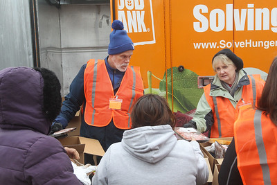 Candace H. Johnson-For Shaw Media Volunteers Tom Myers, of Lake Villa and Cherrie Lozada, of Vernon Hills hand out frozen meat to clients at the Rx Mobile Pantry at the Round Lake Library. The next pantry will arrive at the library on December 3rd from 12-2:00 pm. (11/19/19)