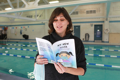 """Candace H. Johnson-For Shaw Media Christa Lawrence, marketing manager for the Mundelein Park & Recreation District, reads a page from her new book titled, """"My New Mask,"""" next to the indoor pool at the Mundelein Community Center. Proceeds from the book benefit the Mundelein Parks Foundation.The story is told twice, once in English and once in Spanish.(11/2/20)"""