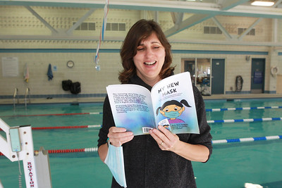 """Candace H. Johnson-For Shaw Media Christa Lawrence, marketing manager for the Mundelein Park & Recreation District, reads a page from her new book titled, """"My New Mask,"""" next to the indoor pool at the Mundelein Community Center. Proceeds from the book benefit the Mundelein Parks Foundation. The story is told twice, once in English and once in Spanish.The book can be purchased at the community center or on Amazon for $10 each. (11/2/20)"""