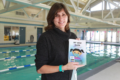 """Candace H. Johnson-For Shaw Media Christa Lawrence, marketing manager for the Mundelein Park & Recreation District, holds her new book titled, """"My New Mask,"""" next to the indoor pool at the Mundelein Community Center. Proceeds from the book benefit the Mundelein Parks Foundation. (11/2/20)"""