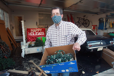Candace H. Johnson-For Shaw Media Terry Weppler, mayor of Libertyville, carries a box of holiday lights out of his garage to decorate his home in Libertyville. The mayor encourages residents to go all out with holiday decorations this year for Light Up Lake County.  (11/4/20)