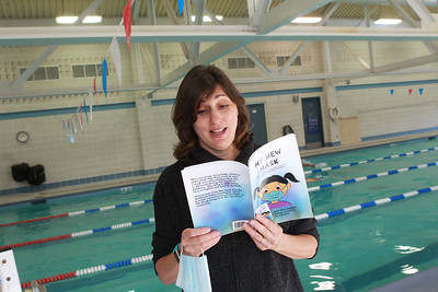 """Candace H. Johnson-For Shaw Media Christa Lawrence, marketing manager for the Mundelein Park & Recreation District, reads a page from her new book titled, """"My New Mask,"""" next to the indoor pool at the Mundelein Community Center. Proceeds from the book benefit the Mundelein Parks Foundation. The story is told twice, once in English and once in Spanish. (11/2/20)"""