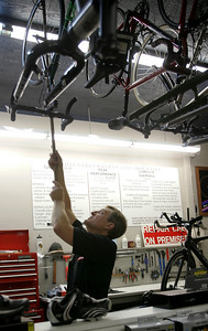 Monica Maschak - mmaschak@shawmedia.com Bob Olsen unhooks a bike from the ceiling of his store, Water Werks, in Crystal Lake.  He will be riding this bike over the Andes Mountains as part of Pacific Atlantic Cycling Tours.