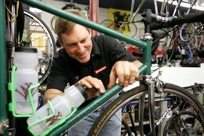 Monica Maschak - mmaschak@shawmedia.com Wheel Werks owner Bob Olsen, 44, of Crystal Lake applies a decal of his business to a custom-built bike he plans on taking to Peru as part of a humanitarian cycling tour.  Olsen will ride this bike on a 14-day tour with the group Pacific Atlantic Cycling Tours.  He will donate the bike to a child in Lima, Peru.  PAC will also be helping rural villagers get clean drinking water.
