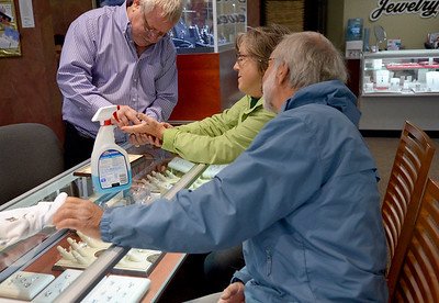 "Monica Maschak - mmaschak@shawmedia.com Nelson's Jewelry co-owner Richard Nelson helps to remove a ring from Suzanne Griem's finger.  Suzanne and her husband, Bob, came to Nelson's to get their wedding bands resized for their 42nd anniversary.  ""We've been customers with Nelson's for a long, long time,"" Bob said. The family-owned jewelry store in Crystal Lake has been in business for 50 years."