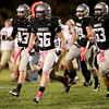 Kaneland players celebrate taking over on downs during the first quarter of their home game against Morris Friday night.