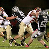 Morris quarterback Zach Cinnamon is pursued by Kaneland's Justin Diddell (53) during their game at Kaneland Friday night.