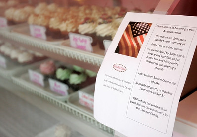 Monica Maschak - mmaschak@shawmedia.com A sign on the display case in SweetPea Cakes lets customers know about the John Larimer Boston Cream Pie cupcakes in honor of John Larimer, an Aurora, Colo., shooting victim and Crystal Lake resident.