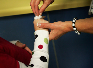 Monica Maschak - mmaschak@shawmedia.com Stevenson treats a student's cut before applying a bandage.