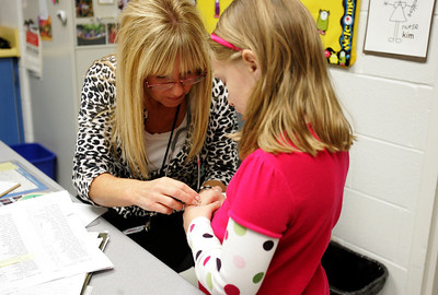 Monica Maschak - mmaschak@shawmedia.com Eastview Elementary School's nurse Kim Stevenson, assesses a cut on a student's hand Friday in Algonquin. Stevenson said she typically sees about 500 students a month.  The 31 nurses in D300 oversee about 20,000 students.