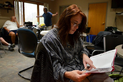 Monica Maschak - mmaschak@shawmedia.com Therese Page, 49, looks through job postings at the Public Action to Deliver Shelter's Day Services Center in Woodstock Monday.  Page came to PADS after her house was foreclosed.  The shelter is part of the Continuum of Care, which includes Home of the Sparrow, Transitional Living Services, and Thresholds, and they all work to get temporary and permanent housing for homeless people.