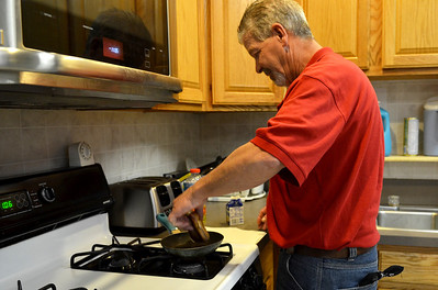 "Monica Maschak - mmaschak@shawmedia.com John Stott, 56, makes a grilled ham and cheese sandwich in the kitchen of the PADS Day Services Center.  At this center, clients can shower, wash their laundry and make meals in the kitchen.  Stott plans to one day ""go to Arizona and start a detailing shop."""