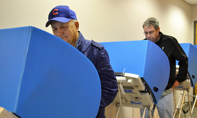 "Monica Maschak - mmaschak@shawmedia.com Russell Johnson, 75, and Rich Crosbie, 61, use electronic voting machines to cast their vote Monday at McHenry City Hall, McHenry.  ""My mind is already made up.  There's no need to wait,"" Crosbie said.  Registered voters can electronically vote early up to 5 days prior to Election Day."