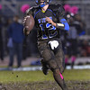 The mud flies as St. Charles North quarter back Erik Miller rolls out during their home game Friday Oct. 19 against South Elgin.<br /> Staff photo by Mark Busch