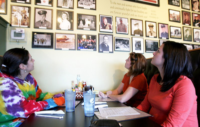 """Monica Maschak - mmaschak@shawmedia.com Jackie deLeon (left), Jennifer Rose and Kelly Harte from McHenry admire the  veterans wall inside Kim and Patty's Cafe on Wednesday.  """"It's a nice way to comemorate them,"""" deLeon said.  The photographs of the veterans now extend to two walls of the restaurant.  Military family members can be seen grouped together on the wall."""