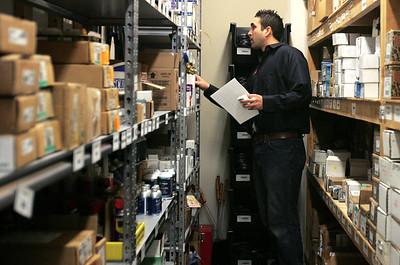 Monica Maschak - mmaschak@shawmedia.com Warehouse manager Clay Bierdeman retrieves supplies in the stock room of the Approved Comfort Heating & Air Conditioning store Wednesday.  Technicians provide a list of furnace parts and supplies they need Bierdeman to replenish.