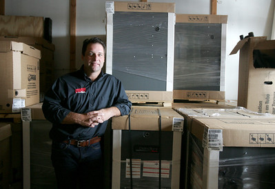 Monica Maschak - mmaschak@shawmedia.com Approved Comfort Heating & Air Conditioning owner Dan Martin poses with a new shipment of Amana furnaces in his Lake in the Hills store Wednesday.