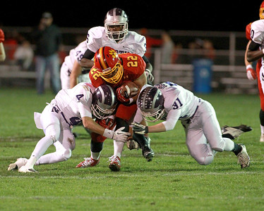 Anthony Thielk (22) of Batavia is tackled by Downers Grove North's Stephen Kanis (4) and Gareth Jones (31) during their first-round playoff game Friday night in Batavia.