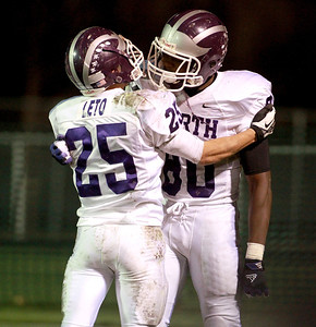 Downers Grove North's Kyle Leto and Richard Olekanma celebrate Olekanma's touchdown during their first-round playoff game North Friday night in Batavia.