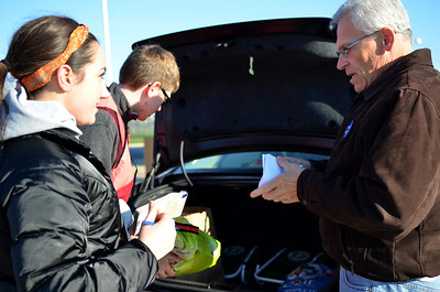 """Monica Maschak - mmaschak@shawmedia.com The Marian Central Catholic High School junior Kristen Hartlieb (left) takes inventory as Robert Morehead unloads donations from Rodger Kriewaldt's car Saturday.  The School's National Honor Society held a """"Spooktacular Donation Drive"""" to help needy families and the disabled in McHenry County by accepting donations of clothing, household items, paper products, toys and nonperishable food items."""