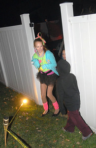 Carly Snyder, 11, of Lombard, gets startled as she walks around the corner. Kris and Marcella Veneziano decorate the backyard of their Lombard home for Halloween with an outdoor haunted house and invite friends and neighbors on Wednesday, Oct. 31, 2012. Staff photo by Bill Ackerman