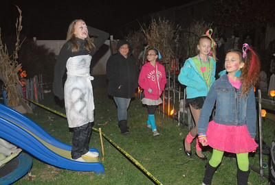 After standing as still as a statue, Kylee Veneziano (from left) comes screaming to life for Beth O'Brien; her daughter, Hanna, 11; Carly Snyder, 11; and Savanah Salvino, 11, walk through Kris and Marcella Veneziano's backyard  on Wednesday, Oct. 31, 2012. The family decorates the backyard of their Lombard home for Halloween with an outdoor haunted house and invite friends and neighbors. Staff photo by Bill Ackerman