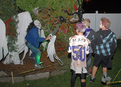 A ghoul leaps out of the bushes on Wednesday, Oct. 31, 2012. Kris and Marcella Veneziano decorate the backyard of their Lombard home for Halloween with an outdoor haunted house and invite friends and neighbors. Staff photo by Bill Ackerman