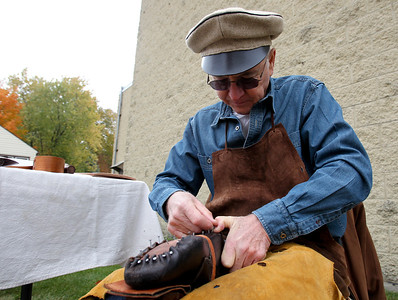 Mike Greene - mgreene@shawmedia.com Mid-West Tool Collectors Association member Norman Walzer, of DeKalb, sets a nail in a leather shoe while demonstrating authentic shoemaking during the 35th annual Cider Fest Sunday, October 7, 2012 at the McHenry County Historical Society Museum in Union. The annual event featured harvest demonstrations, displays and demonstrations of old tools, musical entertainment, barn raising, apple goodies bakery, white elephant sale and more.