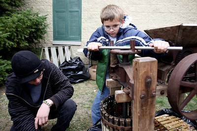 Mike Greene - mgreene@shawmedia.com Alex Parrott, 11 of Machesney Park, twists a machine to crush apples for apple cider as volunteer Nick Caldrone helps during the 35th annual Cider Fest Sunday, October 7, 2012 at the McHenry County Historical Society Museum in Union. The annual event featured harvest demonstrations, displays and demonstrations of old tools, musical entertainment, barn raising, apple goodies bakery, white elephant sale and more.