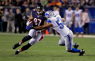 Sarah Nader - snader@shawmedia.com Chicago's Kellen Davis (left) is tackled by Detroit's DeAndre Levy while he runs a play during the second quarter of Monday's game at Solider Field in Chicago on October 22, 2012.