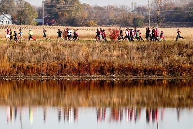 Josh Peckler - Jpeckler@shawmedia.com Runners pass by a pond as they participate in The 12th annual Care 4 Breast Cancer 5K Run/Walk at Woodstock North High School Sunday, October 21, 2012.