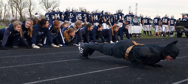 Monica Maschak - mmaschak@shawmedia.com Cary-Grove senior Ian May (Right) leads the cheerleaders in doing 41 push-ups just after the Trojans scored 41 points against the Auburn Knights Saturday.