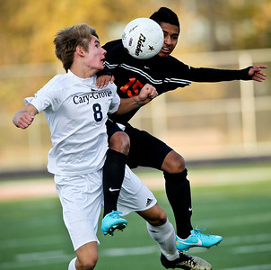 Josh Peckler - Jpeckler@shawmedia.com Cary-Grove's Charlie McKune (8) and Mchenry's Geronimo Hernandez battle for a ball in the air during the first half of a IHSA regional semi-final game at Barrington High School Tuesday, October 16, 2012. Cary-Grove went on to defeat McHenry 2-0.
