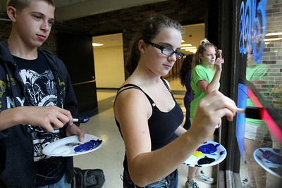 Mike Greene - mgreene@shawmedia.com Sophomore Nick Schoenhoft, 15, helps classmate Liz Beatty, also 15, while painting during window decorations for homecoming Wednesday, October 3, 2012 at Cary-Grove High School in Cary. Homecoming festivities will culminate in parades Saturday morning before a varsity home football game against Huntley at 1PM.