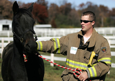 Monica Maschak - mmaschak@shawmedia.com Brian Mark, of the Woodstock Fire Department, leads a horse back to the instructor after a demonstration on capturing a loose horse in Woodstock on Saturday.